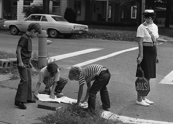 "THE GOSHEN NEWS | August 27, 1974<br /> Things were ""quite hectic"" in homes and schools in Goshen today as youngsters, parents, teachers and school administrators adjusted from their carefree summer schedule to the opening of school days. Elementary students reported this morning for only an enrollment period, but teachers were on duty for their first full day of school. Just getting to school today was an effort for Gene and Ronnie Hunter, who dropped books and notepaper in the street as they crossed to Chandler School. Gene and Ronnie hurriedly pick up the school supplies while Hector Rivera gives advice and Mrs. Ethlyn Riley, Chandler crossing guard, keeps a watchful eye."