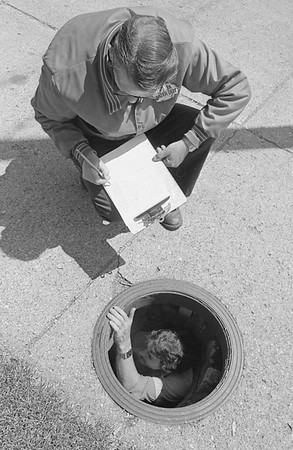 THE GOSHEN NEWS | May 21, 1981<br /> Some water meters are harder to read than others. Steve Cripe is shown in the manhole reading off the numbers to Jim Forsch in what was a two-man job Wednesday reading a meter on the east side of the Elkhart County Courthouse. Fortunately, not all water meters in Goshen are this difficult to read. One advantage, though, is that the meter readers never have to worry about no one being home.
