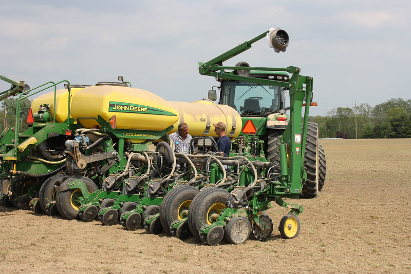 HALEE HEIRONIMUS / GAZETTE Jeff Miller, left, finishes planting corn in a field in Penfield Township.