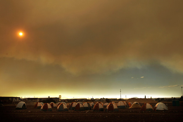 Arizona Wildfires.JPEG-0bfd.JPG Smoke from the Wallow Fire fills the sky over tents where firefighters are sleeping at an incident command center in Eagar, Ariz., Thursday, June 9, 2011. (AP Photo/Marcio Jose Sanchez)