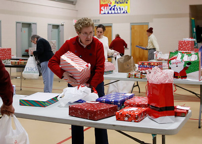 Arlington Community members prepare gifts for the Red Stocking program. 122016