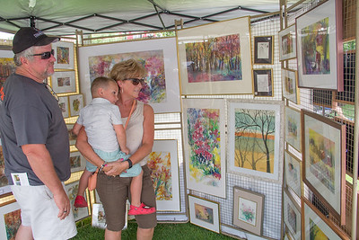 ALEC SMITH / GAZETTE The 43rd Art In The Park fine art exhibit and sale took place Sunday in Public Square in Medina. Todd Giesen, Lori Giesen and 3-year-old son Carter look at the watercolor work of Helga Lunkwitz.