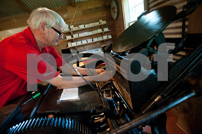 David Jones of Hideaway puts a custom plate for a recipe card on his 1898 Chandler Price printing press at a cabin on family's land in Arp, Texas June 26, 2015. Jones and Denys Smith run the Etsy shop Alias Smith and Jones which sells items such as coasters and wooden cards with custom images made from the printing press.   (photo by Sarah A. Miller/Tyler Morning Telegraph)