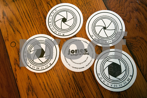Coasters such as these are one of the types of items David Jones and Denys Smith of Hideaway create with a 1898 Chandler Price printing press.  (photo by Sarah A. Miller/Tyler Morning Telegraph)