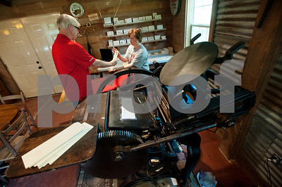David Jones and Denys Smith of Hideaway create custom printed wooden recipe cards using an 1898 Chandler Price printing press at a cabin on family land in Arp, Texas June 26, 2015. Jones and Smith run the Etsy shop Alias Smith and Jones which sells items such as coasters and wooden cards with custom images made from the printing press.   (photo by Sarah A. Miller/Tyler Morning Telegraph)