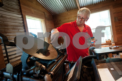 David Jones of Hideaway puts ink on the plate of his 1898 Chandler Price printing press as he prepares to fill an Etsy order in Arp, Texas June 26, 2015. Jones and Denys Smith run the Etsy shop Alias Smith and Jones which sells items such as coasters and wooden cards with custom images made from the printing press.   (photo by Sarah A. Miller/Tyler Morning Telegraph)