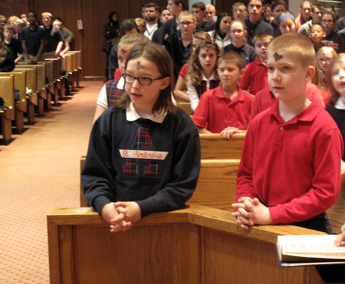 ELIZABETH DOBBINS/GAZETTE St. Ambrose third graders Kylie Belz and Blake Karns stand to sing after they received ashes at Mass on Wednesday.