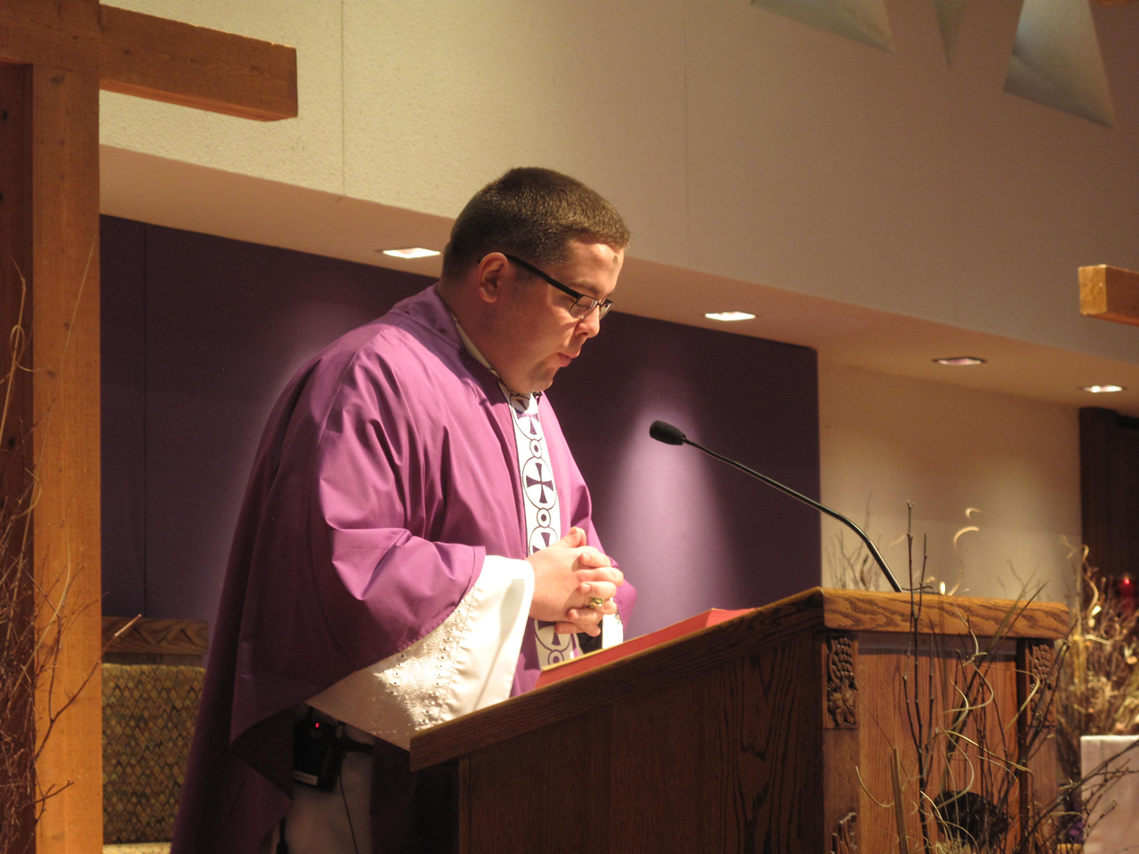 ELIZABETH DOBBINS/GAZETTE The Rev. Rob Ramser reads from the Bible at St. Ambrose's Ash Wednesday Mass.