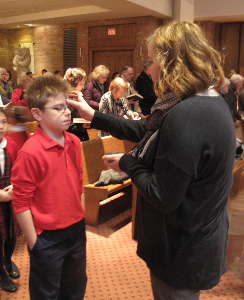ELIZABETH DOBBINS/GAZETTE St. Ambrose third grader Johnie Kyle receives ashes at Ash Wednesday Mass Wednesday. Teacher Stacy Gove administered ashes to St. Ambrose students and other parishioners during the ceremony.