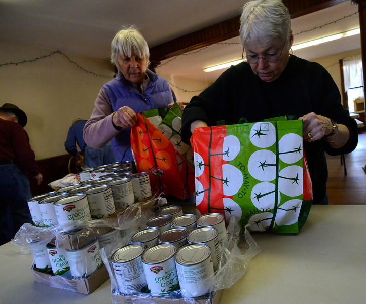 KRISTOPHER RADDER — BRATTLEBORO REFORMER<br /> Pat Haine, director of the Guilford Cares Food Pantry, assembles a bag of food. Seven volunteers from Guilford Cares Food Pantry make 30 Thanksgiving baskets for local families at the Broad Brook Community Center, in Guilford, on Monday, Nov. 25, 2019.