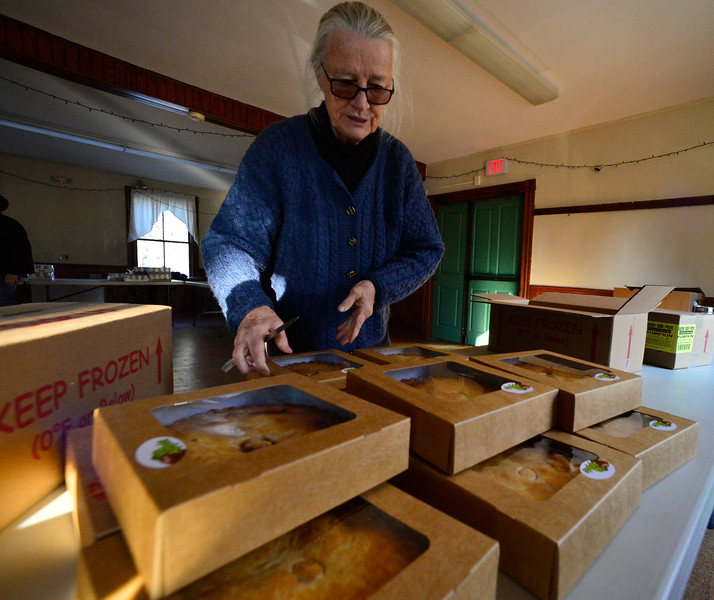 KRISTOPHER RADDER — BRATTLEBORO REFORMER<br /> Diane Frost lays out two different types of pies on the table. Seven volunteers from Guilford Cares Food Pantry make 30 Thanksgiving baskets for local families at the Broad Brook Community Center, in Guilford, on Monday, Nov. 25, 2019.