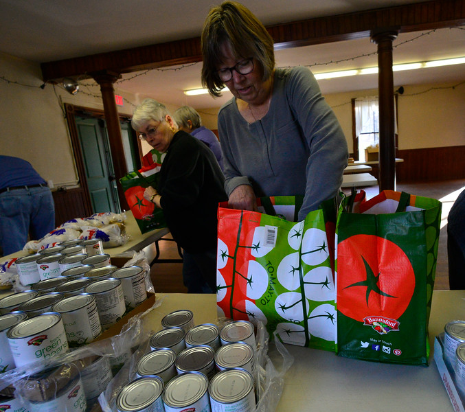 KRISTOPHER RADDER — BRATTLEBORO REFORMER<br /> Barb Borek puts a can of green beans into one of the bags for a family. Seven volunteers from Guilford Cares Food Pantry make 30 Thanksgiving baskets for local families at the Broad Brook Community Center, in Guilford, on Monday, Nov. 25, 2019.