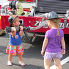 Maggie Marietta, 2, holds a fire hose as her sister Molly, 4, looks on Tuesday evening, Aug. 6, during National Night Out.