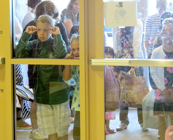 Two Boone Meadow students peer through the glass before entering school Wednesday, Aug. 14.