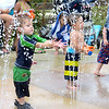 A two-and-a-half-year-old Zionsville boy plays in the sprinklers Friday, July 26, at Mulberry Fields Splash Park.