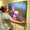 """Melissa Fanning hangs a photograph Thursday afternoon, Aug. 1, at the SullivanMunce Cultural Center. The photograph, Barry Lively's """"Cleome,"""" is one of several new pieces on display at the center."""