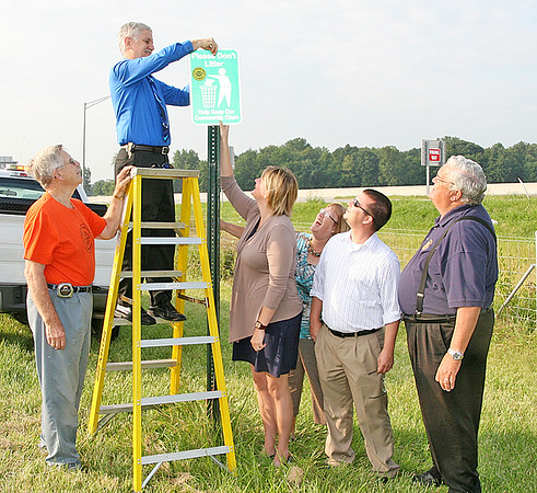 Rod Rose Lebanon Reporter<br /> Mayor Huck Lewis bolts a do-not-litter sign to a stanchion on Perry-Worth Road Tuesday as from left) Jerry Erskine; xxxxx, Tami Richardson, Jim Smith and Rev. Richard Burdett observe.