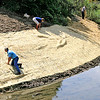Rod Rose The Lebanon Reporter<br /> Boone County Surveyor Ken Hedge and Assistant Surveyor Carol Cunningham smooth straw along the interior bank of Prairie Creek, north of the National Guard Armory in Lebanon, after seeding the bank for erosion control. Contractors removed vegetation, including several trees, and silt to improve the stream's flow, earlier Tuesday.