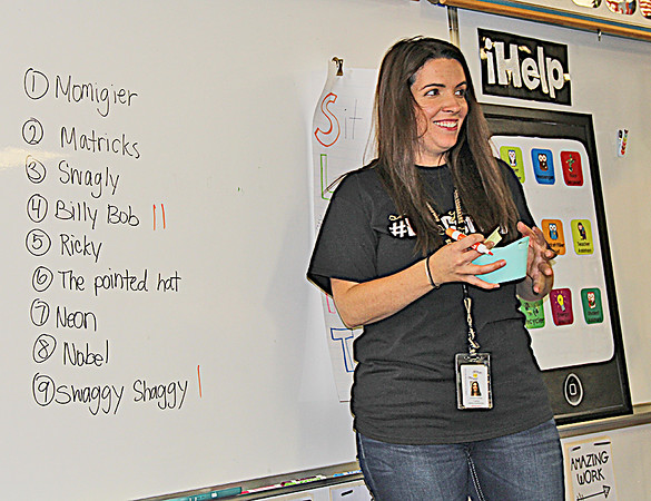 GNOME NAMING: Harney Elementary School fourth-grade teacher Kirlyn Walker tallies her students' votes for the naming of their class mascot, a garden gnome.
