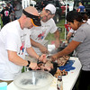 "Team Effort: Swine-N-Dine's (from, left) Monte Jones, Nick Eagle and Veronica Estudillo work together to pull apart pork shoulder prior to the arrival of more than 1,000 attendees that would sample their product. ""Didn't it say rain or shine?,"" said Eagle about the conditions. ""We're just rolling with the punches. Honestly, the weather hasn't affected us much."" Swine-N-Dine went on to win the rub/marinade category."