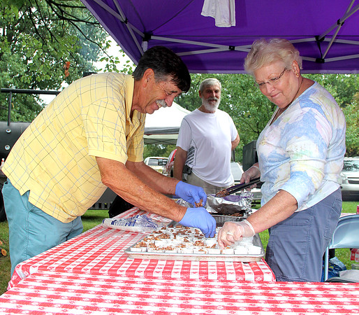"Setting Up: Team Centenary United Methodist Church members (from left) Mark Turner, Bill Price and Claudia Turner work together to put out its raspberry, sweet BBQ samples. ""We're just praying people come out,"" Claudia said."