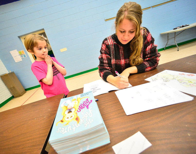 "KRISTOPHER RADDER — BRATTLEBORO REFORMER<br /> Piper Stafford, a kindergartner at NewBrook Elementary School,  smiles as Alexia Pearson, a South Carolina resident and author of ""Adventures of Turbo,"" signs a copy of her book on Tuesday, Jan. 29, 2019."