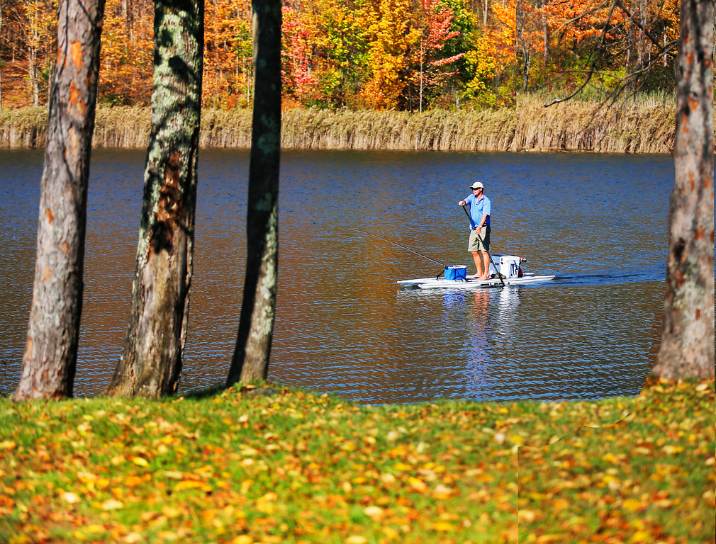 . Holly Pelczynski - Bennington Banner Beau Thebault, of Manchester takes advantage of the warm weather and does some fishing while on a paddleboard barefoot on Lake Paran in North Bennington.