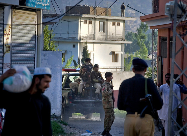 Pakistan army soldiers and police officers patrol past house, background, where it is believed al-Qaida leader Osama bin Laden lived in Abbottabad, Pakistan on Monday, May 2, 2011. Bin Laden, the mastermind behind the Sept. 11, 2001, terror attacks that killed thousands of people, was slain in his hideout in Pakistan early Monday in a firefight with U.S. forces, ending a manhunt that spanned a frustrating decade. (AP Photo/Anjum Naveed)