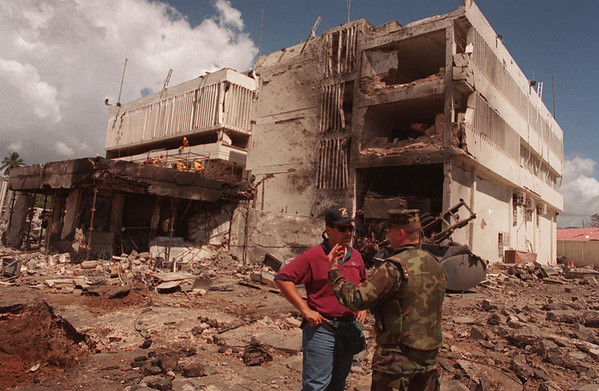 FILE - In this Aug. 15, 1998 file photo, a United States Marine talks with an FBI investigator in front of the damaged U.S. Embassy in the capital Dar es Salaam, Tanzania. Osama bin Laden, leader of the al-Qaida organization behind the Sept. 11, 2001 attacks against the United States and blamed for the 1998 embassy bombings in Kenya and Tanzania, is dead, a person familiar with the situation said late Sunday. (AP Photo/Brennan Linsley, File)