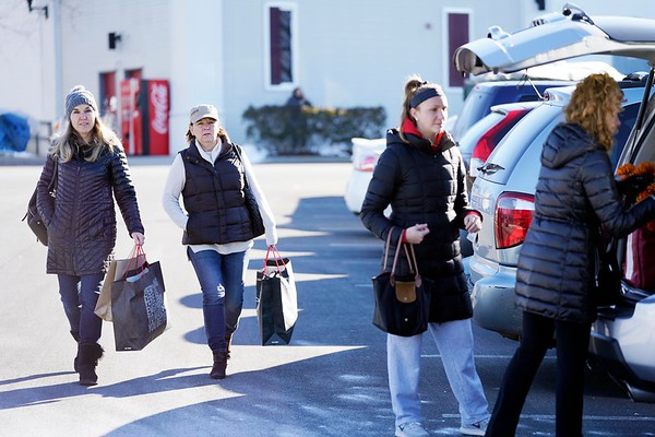 BEN GARVER — THE BERKSHIRE EAGLE<br /> Tammy Stine (knit cap) and Sue Pirog (cap) from South Hampton, Mass., bring the final bags from their haul at Prime outlets in Lee to their rather full SUV.