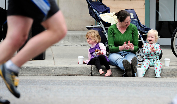 Rebecca Groenendaal (middle) claps with her kids Violet (right), 19 months, and Lilian (left), 3, while watching runners pass during the Bolder Boulder in Boulder, Colorado May 30, 2011.  CAMERA/Mark Leffingwell