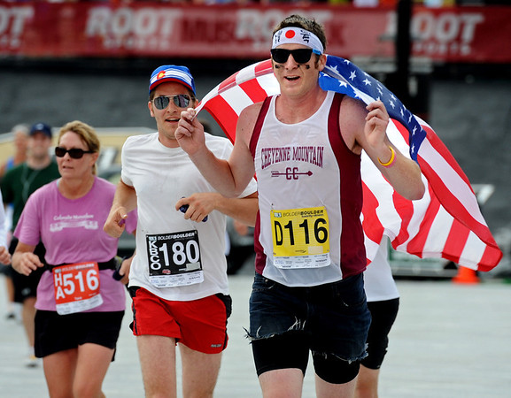 BOLDER<br /> Brett Forrest of Colorado Springs carries the American flag across the finish line at the 2011 Bolder Boulder.<br /> PHOTO BY MARTY CAIVANO<br /> May 30,, 1011