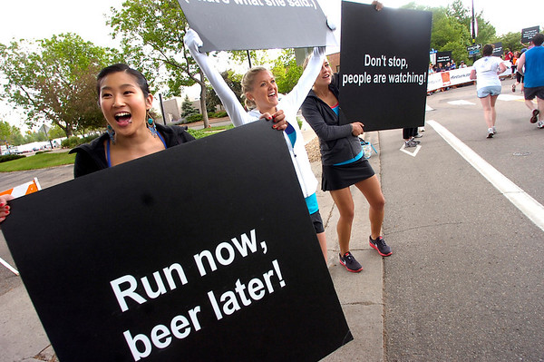 """From left to right Jenny Kershaw, Sarah Ellsworth and Ashley Dixon hold inspirational signs along the Bolder Boulder course.<br /> For more photos and videos go to  <a href=""""http://www.dailycamera.com"""">http://www.dailycamera.com</a><br /> Photo by Paul Aiken  / The Boulder Camera"""