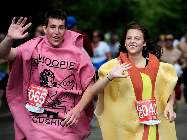 Nick Flore (left), of Highlands Ranch, and Madeline Kovosec (right), of Lakewood, run the race as a whoopie cushion and a hot dog during the Bolder Boulder in Boulder, Colorado May 30, 2011.  CAMERA/Mark Leffingwell