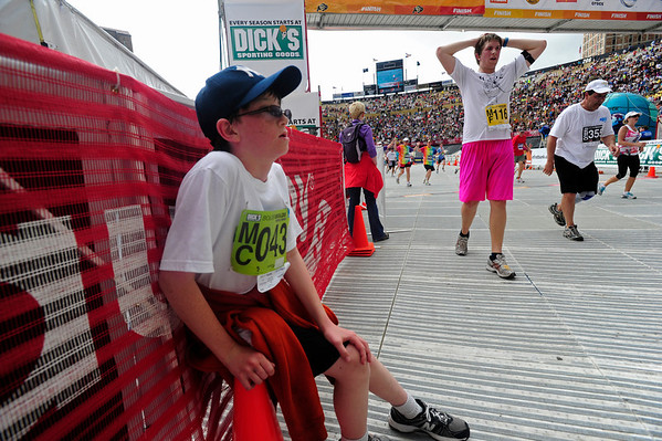 BOLDER<br /> Samuel Chaim-Weissman of Boulder grabs a cone for support after crossing the finish line of the 2011 Bolder Boulder.<br /> PHOTO BY MARTY CAIVANO<br /> May 30,, 1011