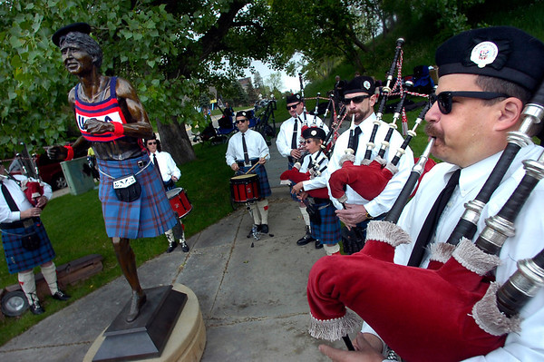 """From left to right Mark McCutcheon and Ben Holmes of the Centennial State Pipe and Drums plays around the statue of Olympic Gold medal winner Frank Shorter at the end of  2011 Bolder Boulder course.<br /> For more photos and videos go to  <a href=""""http://www.dailycamera.com"""">http://www.dailycamera.com</a><br /> Photo by Paul Aiken  / The Boulder Camera"""