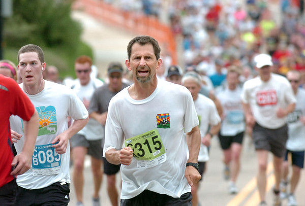 """Jacob Koenig of Centennial, Co runs up the last hill to Folsom Field near the end of  2011 Bolder Boulder course.<br /> For more photos and videos go to  <a href=""""http://www.dailycamera.com"""">http://www.dailycamera.com</a><br /> Photo by Paul Aiken  / The Boulder Camera"""