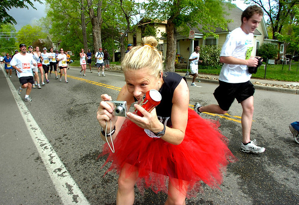 """Amy Perez of Colorado Springs stops to take a beer and a photo of the beer table along the 2011 Bolder Boulder course.<br /> For more photos and videos go to  <a href=""""http://www.dailycamera.com"""">http://www.dailycamera.com</a><br /> Photo by Paul Aiken  / The Boulder Camera"""