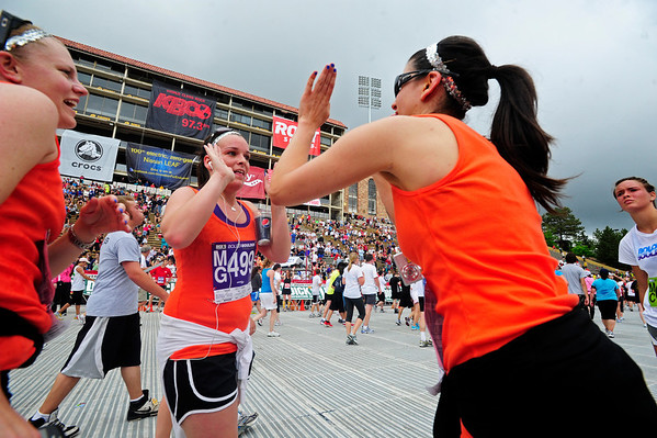BOLDER<br /> Jessica Carlin, right, high-fives Meagan Swanson, center, after they finished the 2011 Bolder Boulder with friend Lindy Thompson, left. <br /> PHOTO BY MARTY CAIVANO<br /> May 30,, 1011