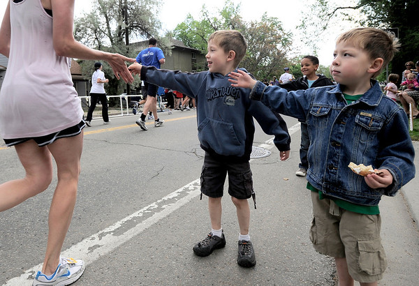 Casey Frye (middle), 6, and Micah Frye (right), 4, get high fives from runners during the Bolder Boulder in Boulder, Colorado May 30, 2011.  CAMERA/Mark Leffingwell