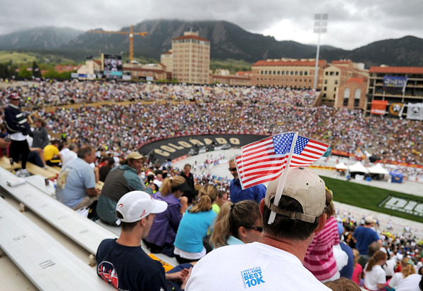 """Chuck Blish, 44, of Arvada, sits in the stands of Folsom Field with american flags tucked in his hat during the Bolder Boulder 10K Race on Monday, May 30, in Boulder. For more photos and video of the Bolder Boulder go to  <a href=""""http://www.dailycamera.com"""">http://www.dailycamera.com</a><br /> Jeremy Papasso/ Camera"""