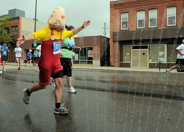 Clive Walker, of Longmont, runs through a sprinkler while dressed as Stewie from Family Guy during the Bolder Boulder in Boulder, Colorado May 30, 2011.  CAMERA/Mark Leffingwell