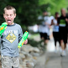 Jake Dimino, 6, takes a break from squirting runners to give himself a little taste of water from his squirt gun during the Bolder Boulder in Boulder, Colorado May 30, 2011.  CAMERA/Mark Leffingwell