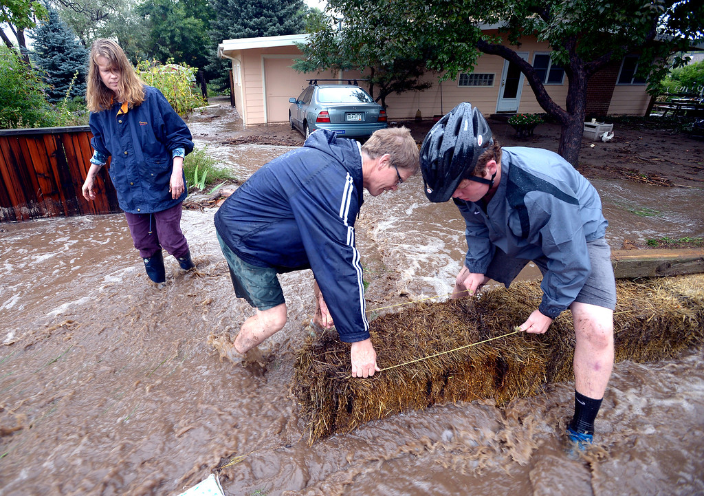 . Kent Shorrock and his wife Astrid Paustian, at left with the help of Patrick Sherman uses straw bales to keep water from their home in North Boulder of Violet Avenue on Friday September 13, 2013 ....Photo by Paul Aiken / The Daily Camera