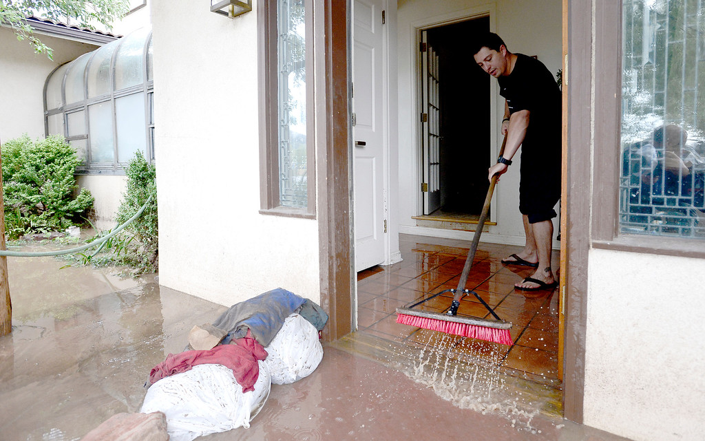 . Lucas Calderon-Griek sweeps water from his home on Upland after heavy rains caused flooding in Boulder, Colorado September 13, 2013. BOULDER DAILY CAMERA/ Mark Leffingwell