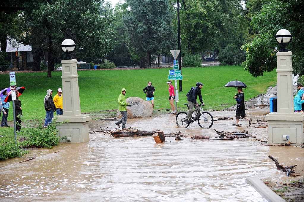 . The Boulder Creek bikepath is washed out in many areas due to the rising water and steady rainfall. Spectators watch the rising water near Broadway Street in Boulder on Thursday, September 12, 2013. (Kira Horvath/ Daily Camera)