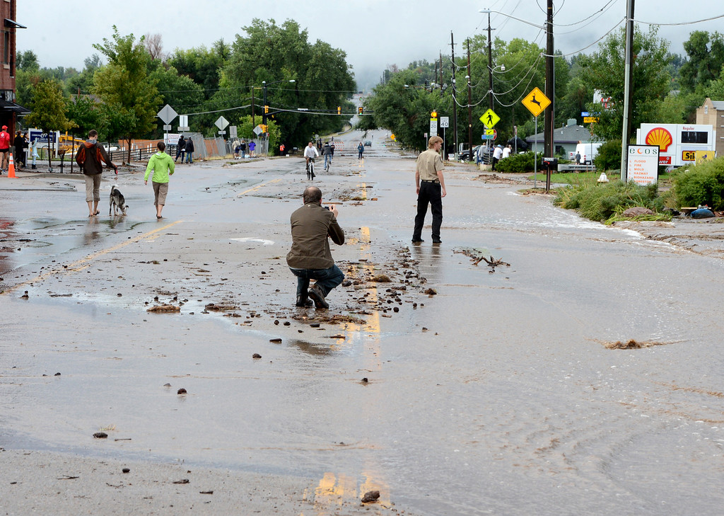 . People look over and photograph the flooding on North Broadway in Boulder on Friday morning. For more flooding videos and photos, www.dailycamera.com. Cliff Grassmick  / September 13, 2013