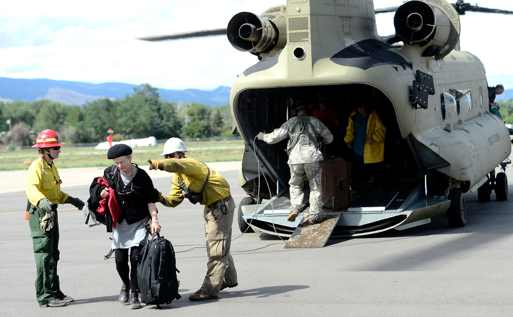 . Deborah Haynes is directed off the tarmac at Boulder Municipal Airport after being flown down from Jamestown on a National Guard helicopter after being stranded from heavy rains in Boulder, Colorado September 13, 2013. BOULDER DAILY CAMERA/ Mark Leffingwell