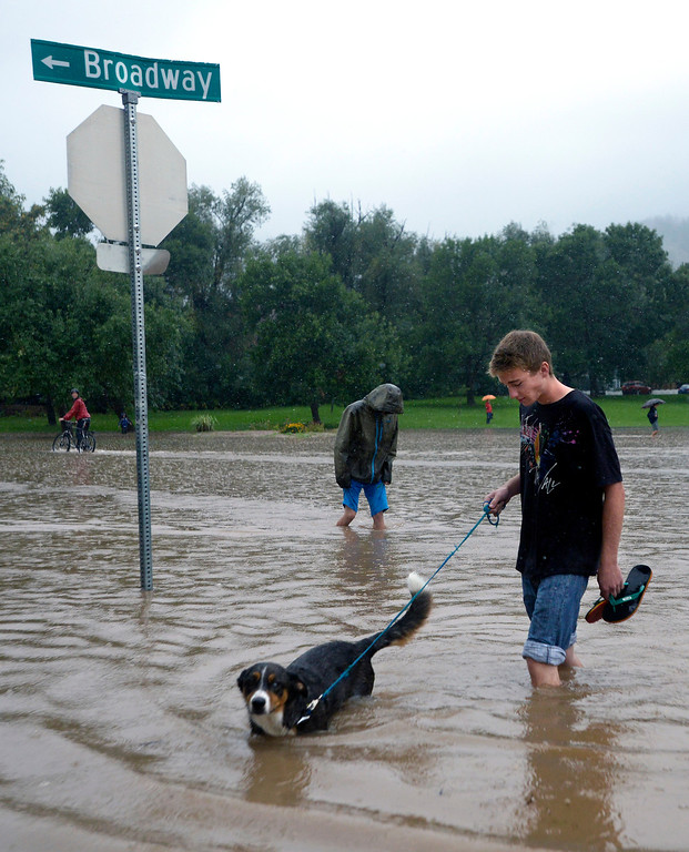 . Rich Easton walks his dog Jax through the flooded street near the North Boulder Park during the heavy flooding on Thursday in Boulder. For a video of the flooding go to www.dailycamera.com  Jeremy Papasso/ Camera