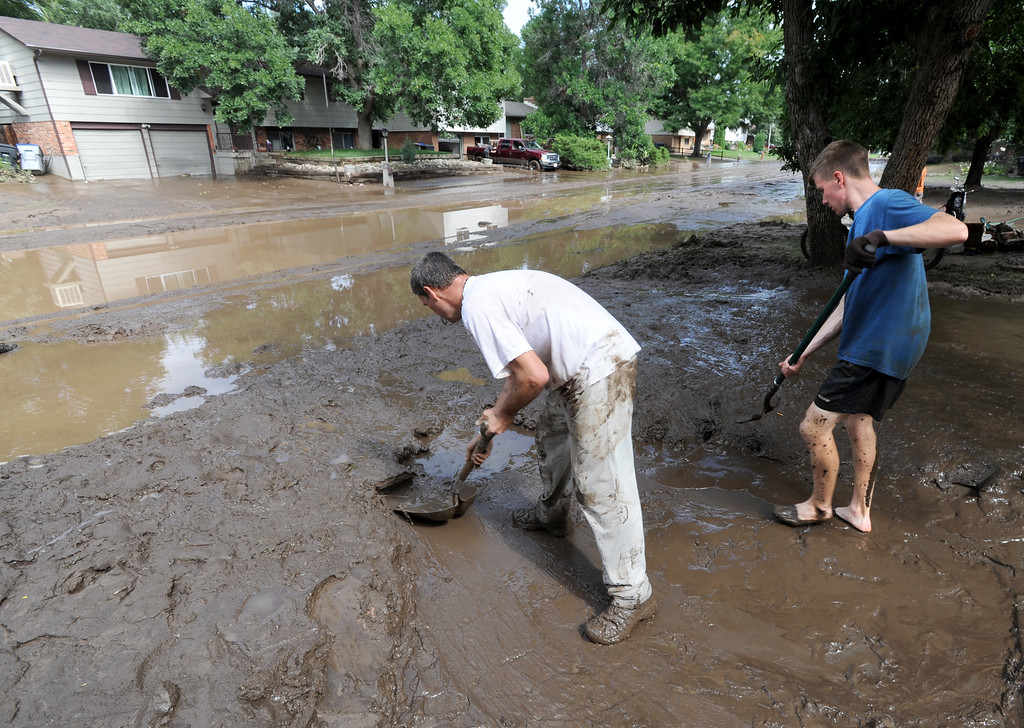 . Mark Swanson, left, and Gabe Anderson, shovel out the mud from this home on Lefthand Drive in Longmont, Colorado, on September 14, 2013. Cliff Grassmick/ September 14, 2013.